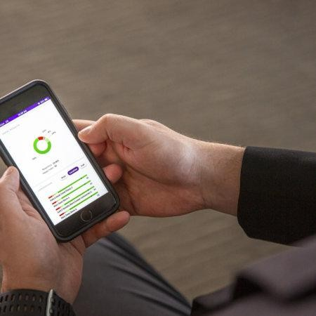Smartphone with graphs showing the HappyOrNot customer feedback reporting online system.