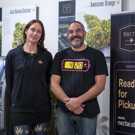Nectar CEO and Director next to curb side pick up scheme sign designed to increase customer experience