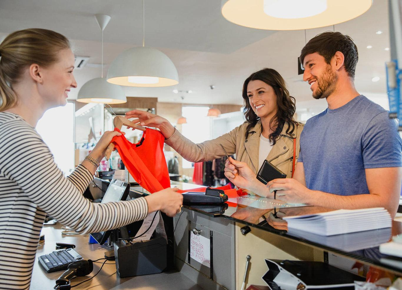 Two customers shopping and laughing at a clothing store expressing joy from their experience