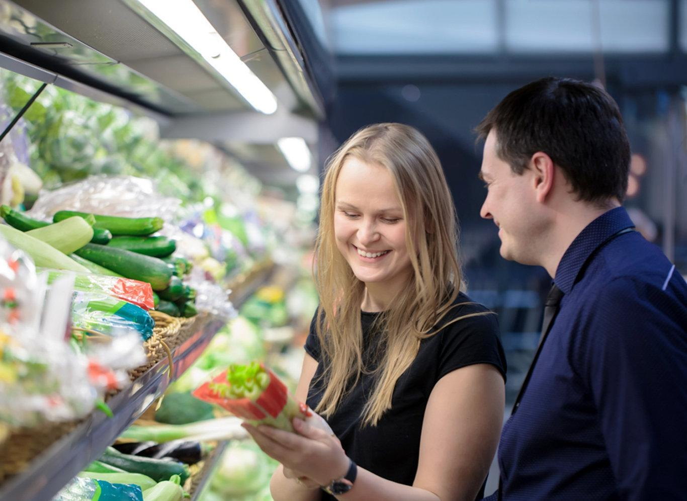Two customers grocery shopping and laughing satisfied from their experience