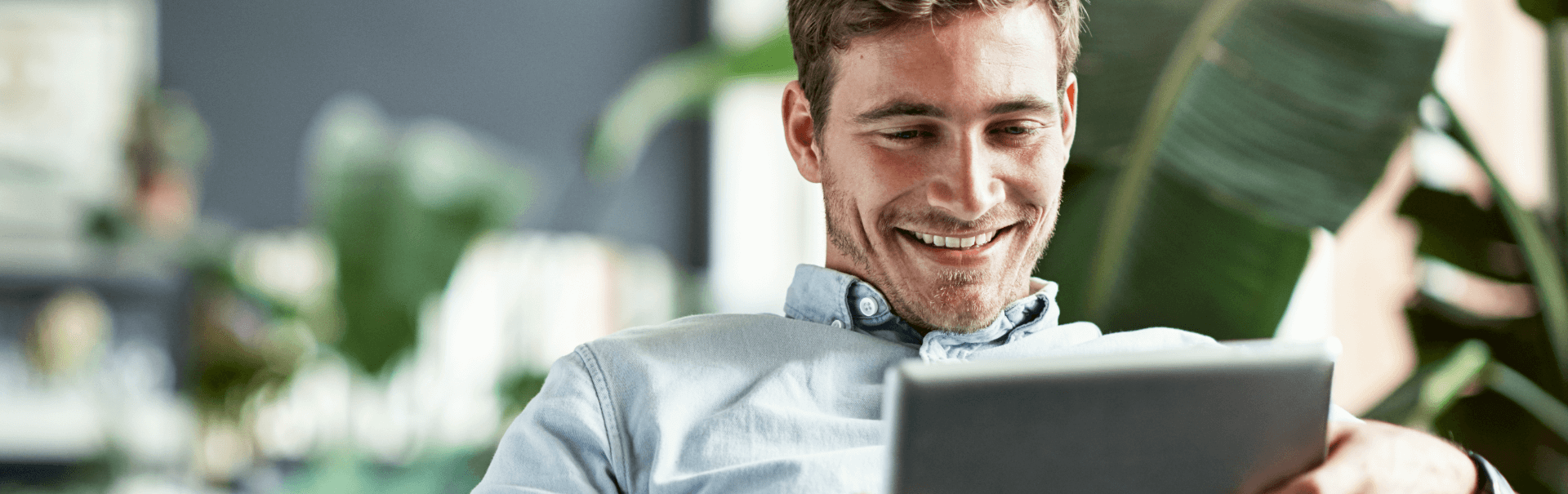 Man smiling while looking at his tablet
