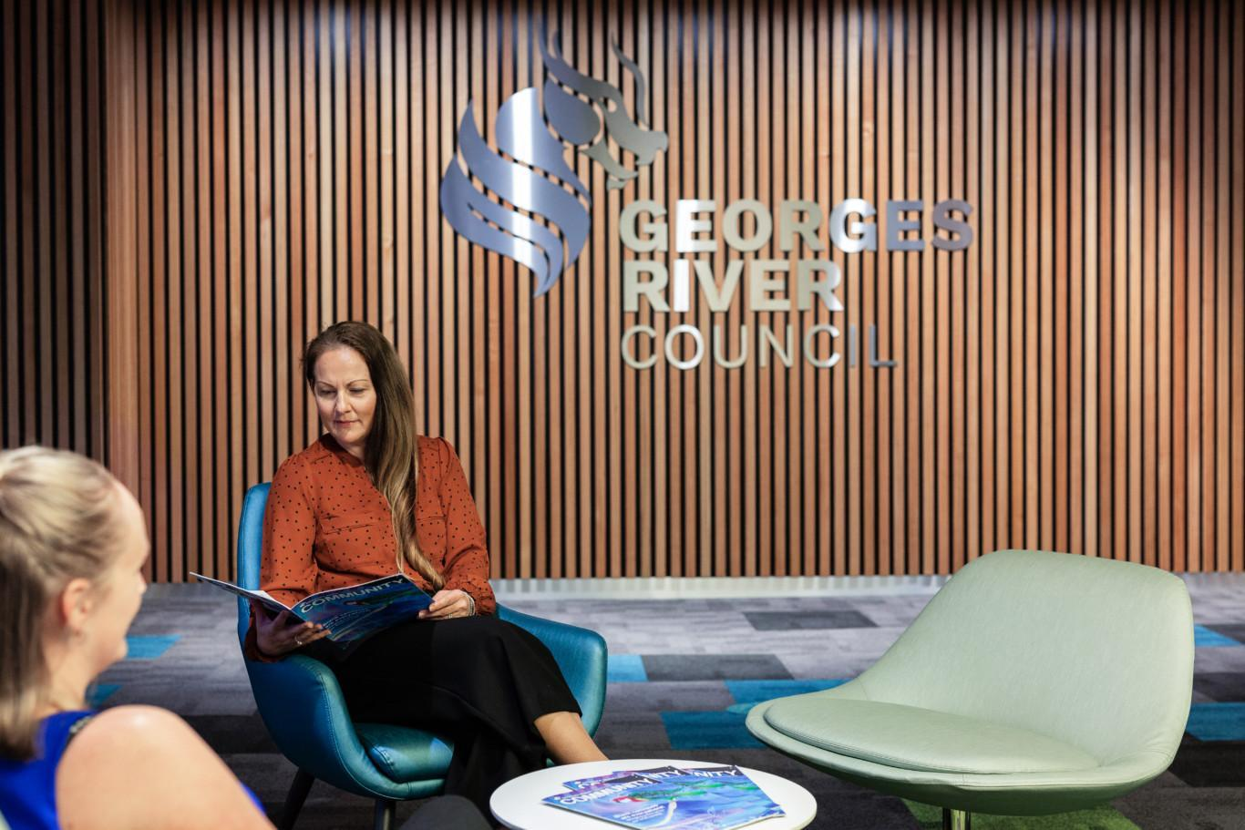Woman sitting at a round table reading a magazine in the lobby of Georges River Council