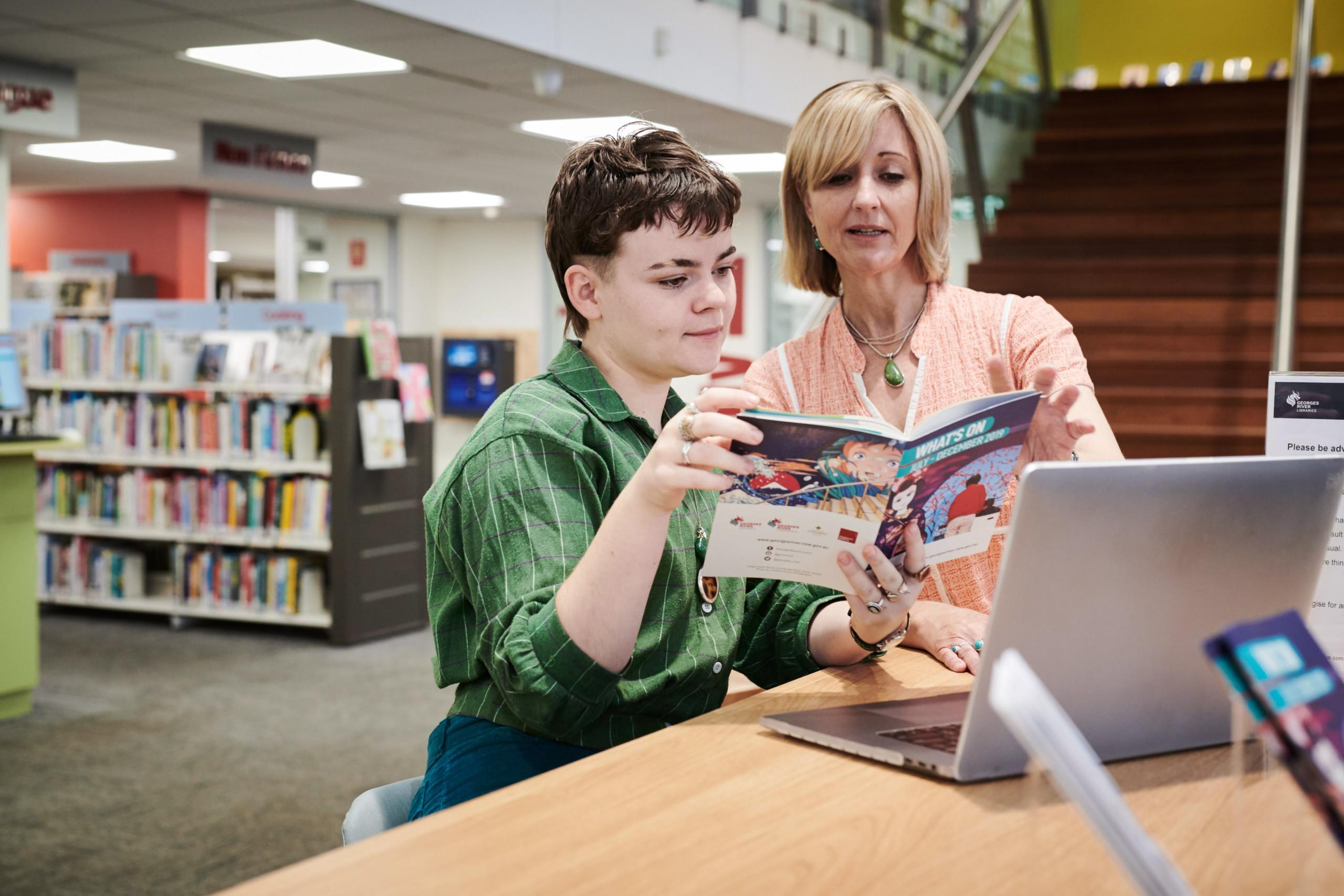 Two women at a library reading a magazine